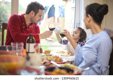 Mother and father cheering with their little girl while having lunch