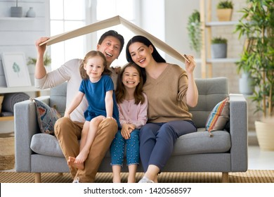 Mother, father and children girls in the room with a symbol of roof. Concept of housing for young family.