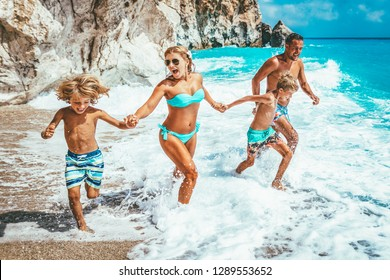 Mother father and children are running on summer beach.