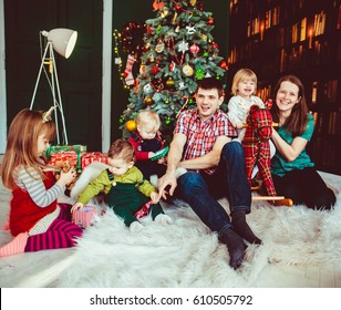 The mother, father and children sitting near Christmas Tree