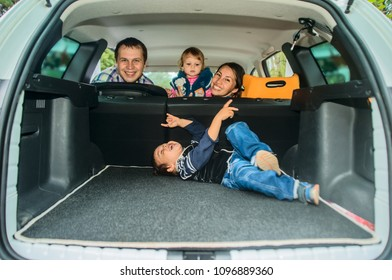 Mother, father and children - son and daughter pretend driving car sitting all on back seats. boy lie ans have fun in trunk. happy family
