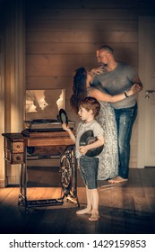 A mother and a father are dancing while their son are choosing gramophone record near the vintage gramophone. Image with selective focus and toning