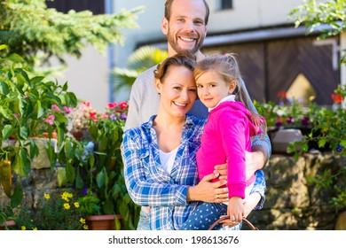 Mother, father and daughter in garden with basket