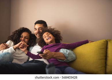 Mother, father and daughter having fun in the living room. Feeling happy and complete.