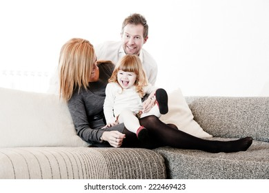 Mother, father and daughter sitting on the sofa & watching a Movie on TV.