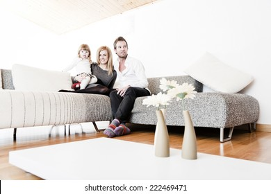 Mother, father and daughter sitting on the sofa.