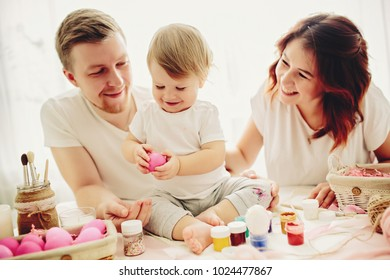 Mother, father and daughters are painting eggs. Happy family are preparing for Easter.