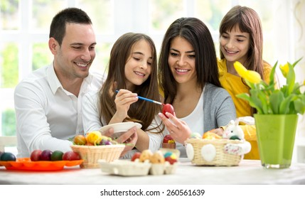 Mother and father with daughters preparing eggs  for Easter