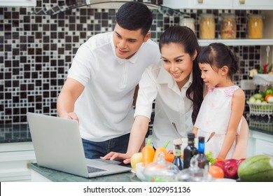 Mother, father and doughter cooking salad menu for dinner by follow clip vdo from internet, this immage can use for internet, clip, family, cooking concept