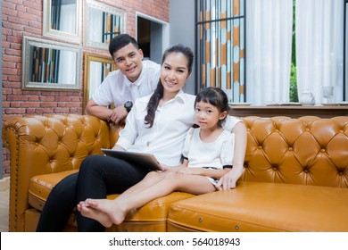 Mother, father and doughter play tablet with wifi internet in vintage family room. Family and techology concept