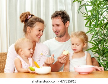 Mother and father Feeding her two daughters. Baby food. In the kitchen interior.