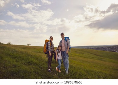 Mother father and girl child with backpacks enjoy on the nature track in summer. Family hikers hiking in the mountains.