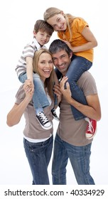 Mother and father giving children piggy back ride against white background