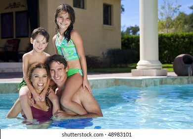 A mother and father having fun on vacation playing with their children on their shoulders in a swimming pool