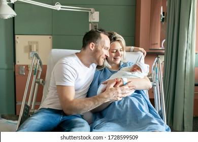 生まれたばかりの赤ん坊を持つ母親と父親が、出産後の1日の入院