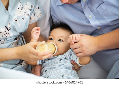 Mother and Father holding  bottle and baby hands to feed milk her baby at home.