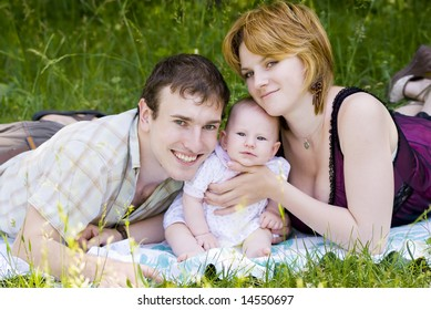 Mother, father and little child relaxing in the park