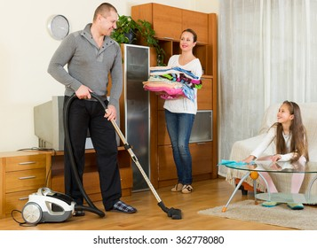 Mother, father and little smiling girl doing general cleaning indoors