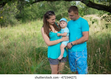mother, father and little son standing under a tree on a beautiful meadow. a happy family. Parents and child