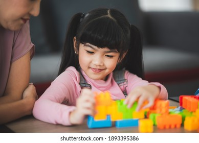Mother and father playing blocks brick toys with her daughter for family time enjoyness at home