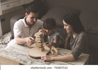 Mother and father playing puzzle game with their daughter in living room together. Family fun time concept.