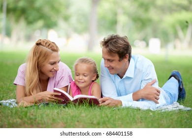 Mother and father reading a book to their daughter