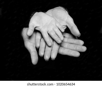 Mother, father and son, family hands black and white image on black background