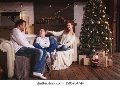 mother, father and son have fun on the sofa by the tree