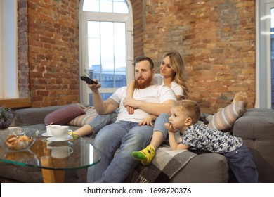 Mother, father and son at home having fun, comfort and cozy, love concept. Looks happy, cheerful and joyful. Beautiful caucasian family. Spending time together, playing, watching cinema, lying on sofa