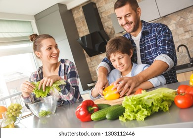Mother father and son at home standing in kitchen together man teaching boy how to cut vegetables smiling cheerful holding his hand with knife