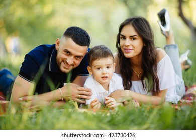 Mother, father and son lying on the grass in park on picnic. Summer family holiday