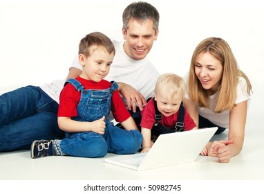 Mother, father and son lying on the floor with laptop
