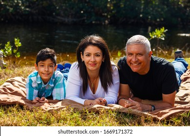 Mother, Father and son outdoor lifestyle portrait in a park setting.