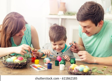 Mother, father and son are painting eggs. Happy family are preparing for Easter.