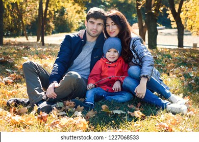 Mother, father and son is sitting on the grass on warm autumn day. Having relax time together.