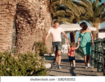 Mother and father with son walk at beach palms. Summer vacation of happy family. Love and trust as family values. Child with father and mother. Family travel with kid on mothers or fathers day