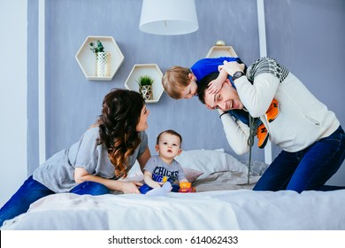 The mother ,father and sons sitting on the bed
