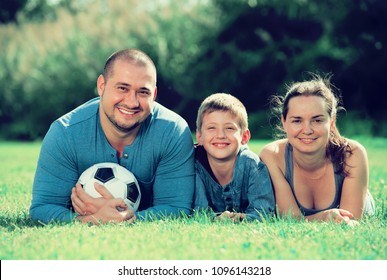 Mother, father and teenager son lying in the grass with soccer ball