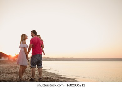mother, father and their child on the beach