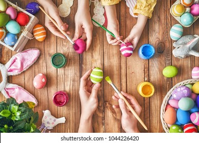 A mother, father and their child painting eggs. Happy family preparing for Easter.