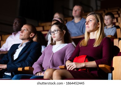 mother, father and their children sitting at perfomance in theatrical auditorium