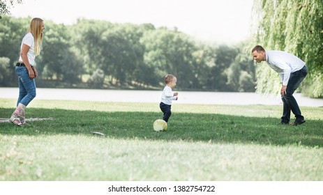 mother, father and their little son are playing with the ball on the lawn.
