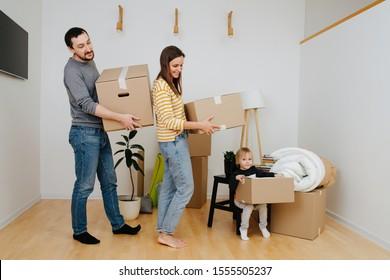 Mutter, Vater und ihr kleiner Sohn, alle halten Kisten in ihren Händen, tragen sie, arrangieren in Stapeln. Sie ziehen von einer alten Wohnung weg und ziehen in ein neues Zuhause um.