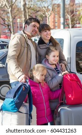 Mother, father and two children with suitcases in journey