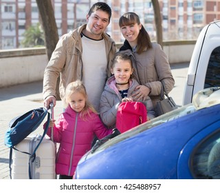 Mother, father and two little daughters with trollers near car