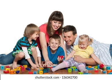 Mother, father, two sons and a daughter are playing together on the floor
