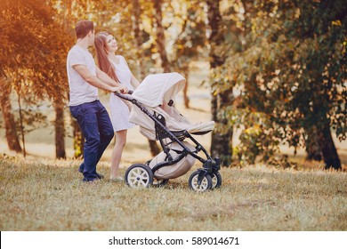 mother and father walk through the park with daughter in stroller