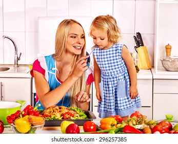 Mother  feed happy daughter child at kitchen .