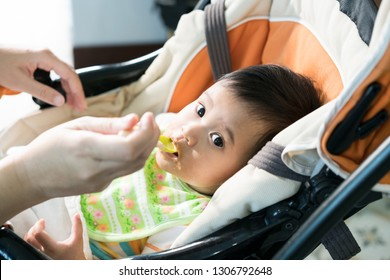 mother feeding 6 months asian baby girl on cart chair. Mom feeds baby homogenized chopped food with a spoon. child care