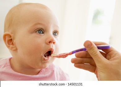 Mother feeding baby food to baby